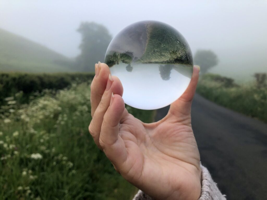 crystal lens ball in a woman's hand, with a refracted view of a misty country lane